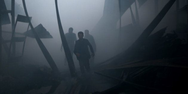 TOPSHOT - Syrian civil defence volunteers, known as the White Helmets, walk amid debris as they extinguish...