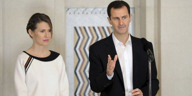 Syria's President Bashar al-Assad stands next to his wife Asma, as he addresses injured soldiers and...