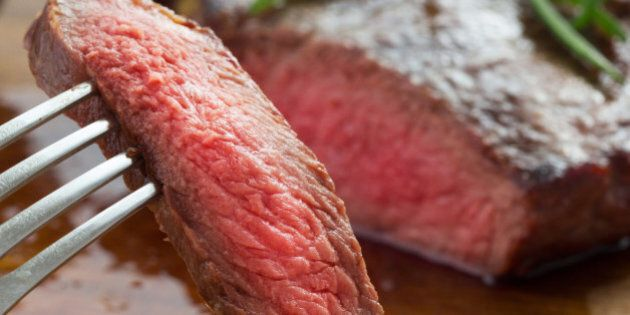 medium roast rib-eye steak on wooden plate with pepper and