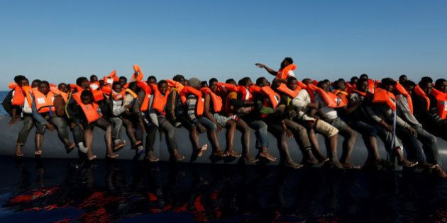 Migrants on a rubber dinghy await rescue by the Malta-based NGO Migrant Offshore Aid Station (MOAS) in...