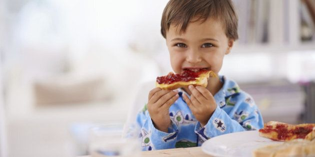 A cute little boy eating toast with jam