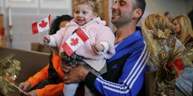 Syrian refugees Kevork Jamgochian holds his daughter Madlin at the St. Mary Armenian Apostolic Church...