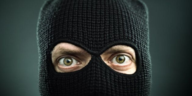 Man with a balaclava looking at camera. Black background.