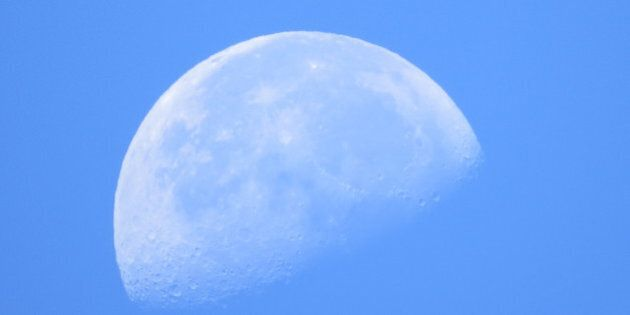 A bright moon in the clear blue sky