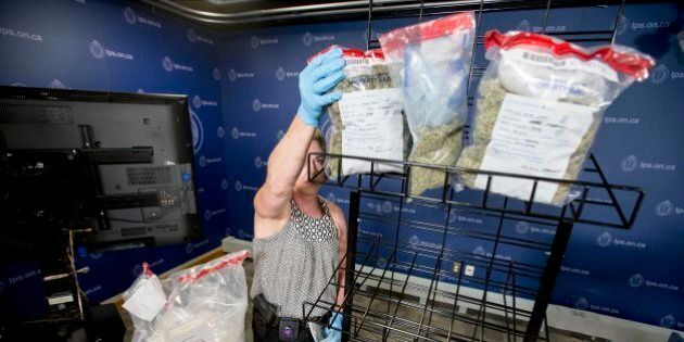 TORONTO, ON - JUNE 3 - Detective Constable with the gun and gangs task force Nadine Teeft removes bags...