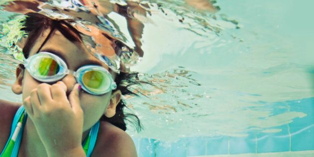 Little girl swimming underwater wearing