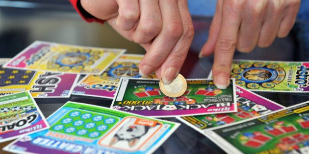 A player scratches a game card of the Française des Jeux (FDJ), the operator of France's national lottery,...