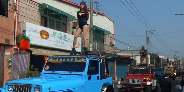 This picture taken on January 3, 2017 shows pole dancers performing on top of jeeps during the funeral...