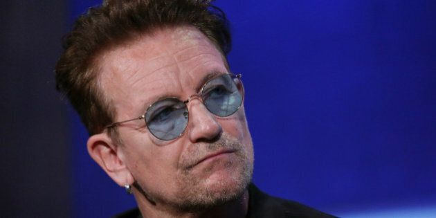 Singer Bono sits during the plenary