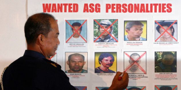Philippine police chief Director General Jesus Verzosa crosses out the picture of Mujibar Alih Amon,...