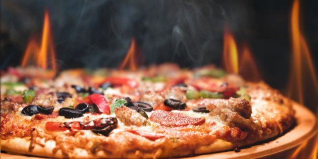 Supreme meat and vegetable pizza on stone in wood-fired oven with open