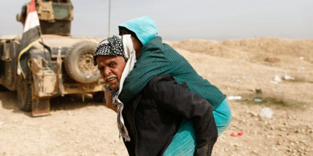 A displaced Iraqi man who fled his home carries a relative as he walks through the desert while Iraqi...