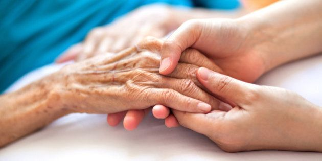 Woman holding senior woman's hand on