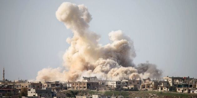 Smoke billows following reported air strikes on a rebel-held area in the southern city of Daraa, on February...