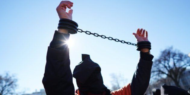 A demonstrator raises his shackled wrists during a protest calling for the closure of the Guantanamo...