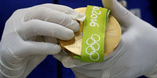 A worker from the Casa da Moeda do Brasil (Brazilian Mint) prepares a Rio 2016 Olympic medal in Rio de...