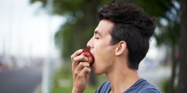 A young man taking a bite of an apple while waiting for the bus