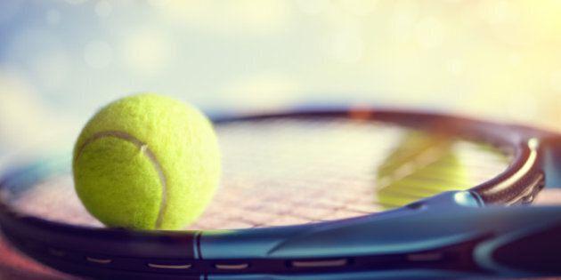 Tennis ball resting on top of a tennis racquet on a red asphalt court