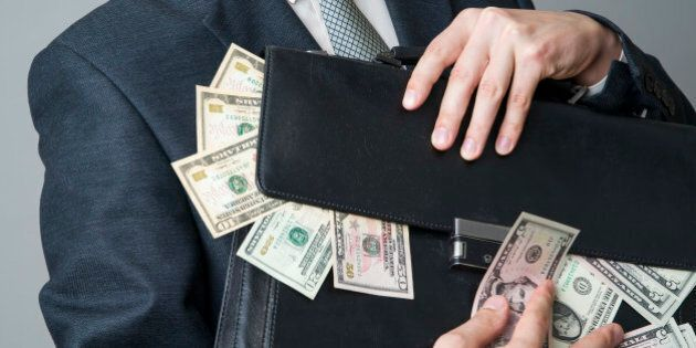 Businessman with a briefcase full of money in the hands of on gray