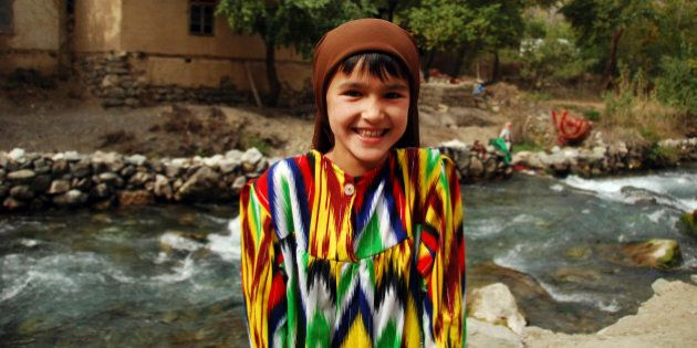 Tajikistan, Penjakent, portrait of local girl in traditional dress by the