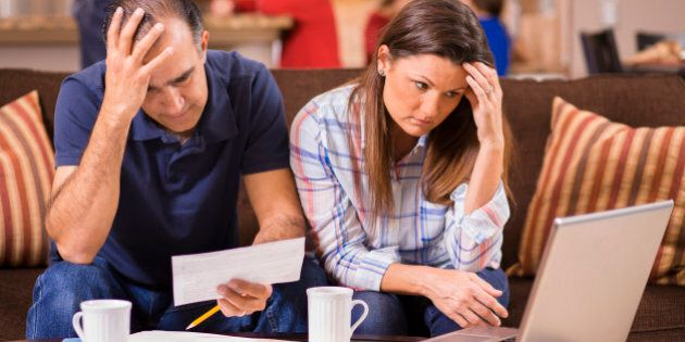 Latin descent man and woman struggle to pay their monthly bills. They are calculating expenses versus...