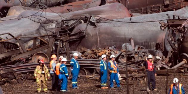 File- In this July 6, 2013 file photo, workers stand before mangled tanker cars at the crash site of...