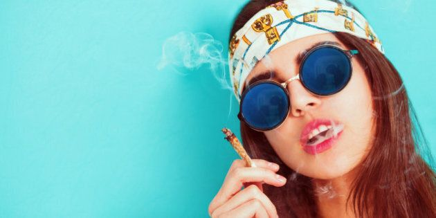 Hippie girl portrait smoking and wearing sunglasses