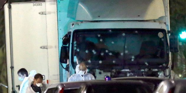Forensic officers stands near a truck with its windscreen riddled with bullets, that plowed through a...