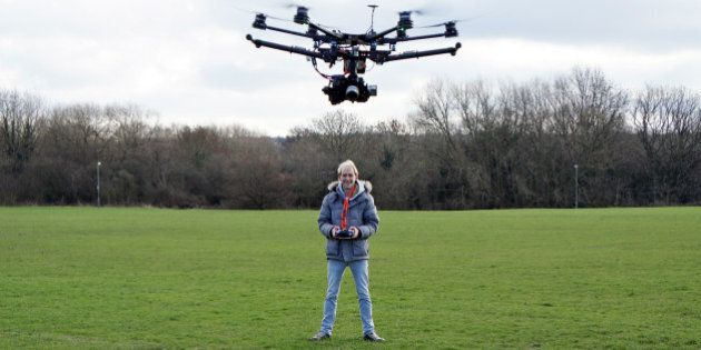 Young man flying a UAV (Unmanned Aerial Vehicle) to capture aerial imagery. Also known as a hexacopter...