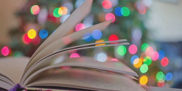 A journal book with colorful holiday christmas lights behind it. The book is open and pages of the book...