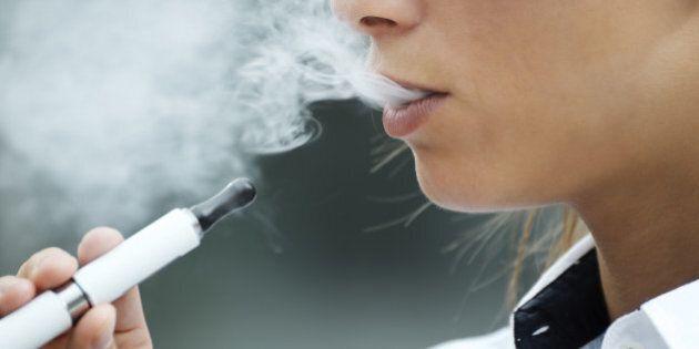 closeup of woman smoking e-cigarette and enjoying smoke. Copy