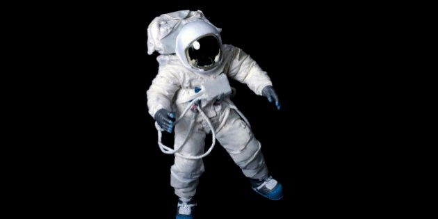Astronaut wearing a plain pressure suit without symbols or insignia against a black
