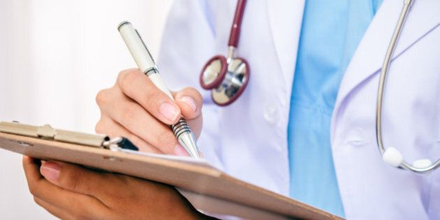 front view of doctor writing information on her folder with a