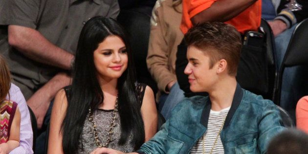 LOS ANGELES, CA - APRIL 17: Selena Gomez (L) and Justin Bieber attend a basketball game between the San...