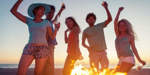Group of friends making party on the beach with fire and