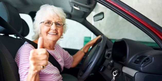 An positive older woman sitting in a car showing a thumbs
