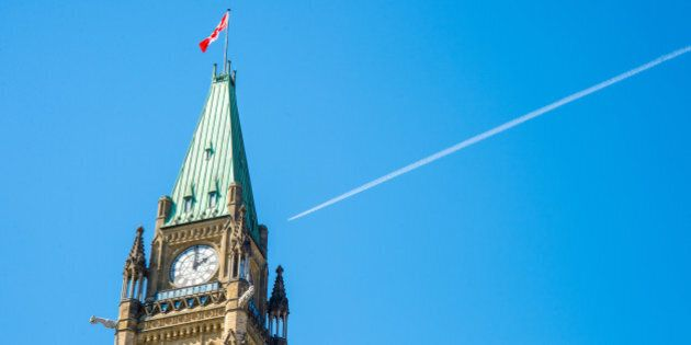 Canadian Parliament Peace tower in Ottawa, with a plane over the blue sky and a white smoke
