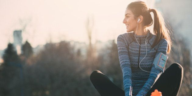 Young beautiful woman resting after the jogging in the city.She is listening to the