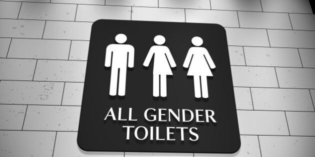A sign on a wall for 'All Gender Toilets with symbols for men, trans and women. LGBT