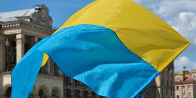 Yellow-blue national banner is fluttering on the wind at the Independence Square in the Ukrainian capital
