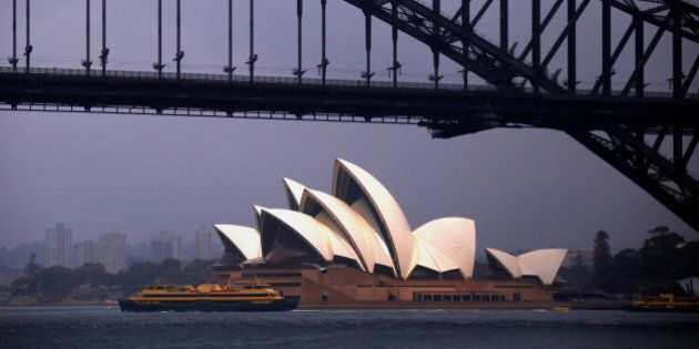 The sun illuminates the Sydney Opera House as a ferry sails past during a storm at Sydney Harbour in...