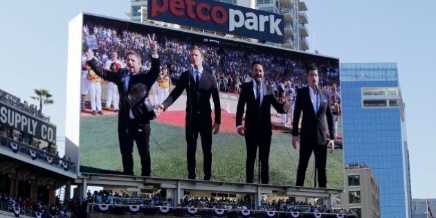 The Tenors, shown on the scoreboard, perform during the Canadian National Anthem prior to the MLB baseball...