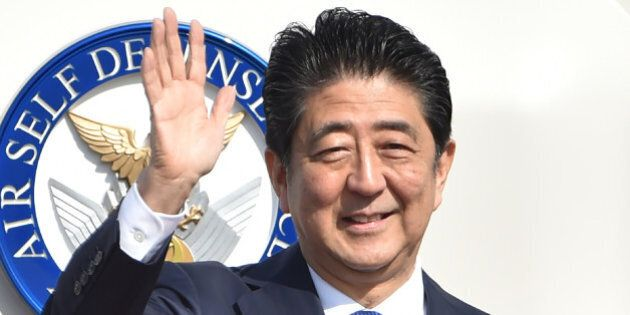 Japan's Prime Minister Shinzo Abe waves to well-wishers prior to boarding a government plane at Tokyo's...