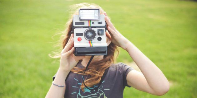 Caucasian girl taking instant photograph outdoors