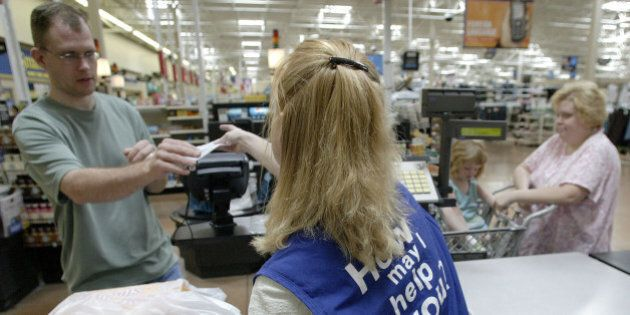 UNITED STATES - AUGUST 15: Louann Cavinder, a cashier at the Wal-Mart store in Grove City, Ohio hands...