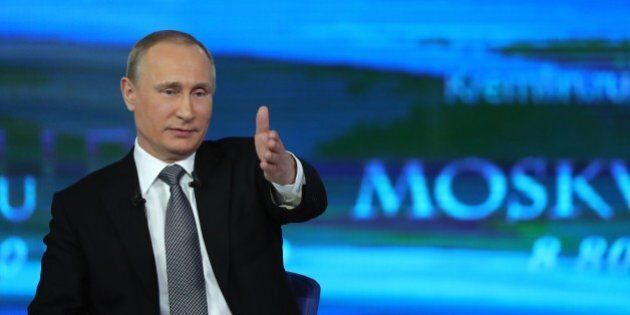 Russian President Vladimir Putin gestures while answering a question during his annual televised call-in...