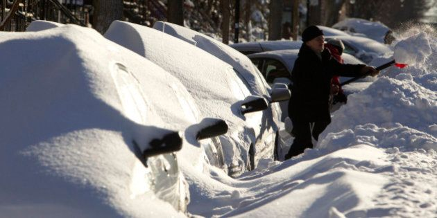 A woman shovels snow next to cars buried under snow in Montreal, December 28, 2012. REUTERS/Olivier Jean (CANADA - Tags: ENVIRONMENT SOCIETY)