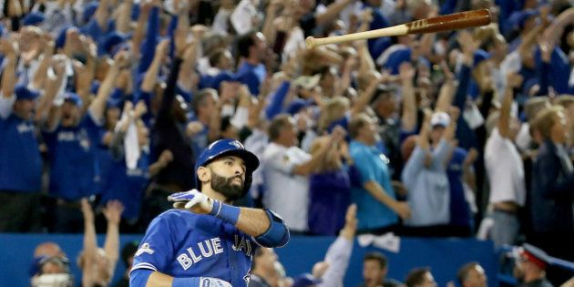 TORONTO, ON - OCTOBER 14: Jose Bautista #19 of the Toronto Blue Jays throws his bat up in the air after...
