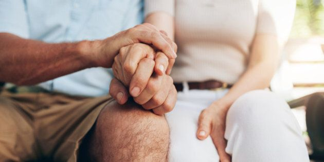 Close up shot of senior couple holding hand. Loving couple sitting together and holding hands. Focus...