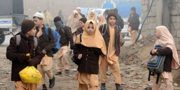 Pakistani children arrive at their school in Peshawar on December 20, 2014, after three days of mourning for the children and staff killed by Taliban militants in an attack on an army-run school. A Taliban massacre at a school is 'Pakistan's 9/11', the country's top foreign policy official told AFP, saying the assault that left 149 dead would change the country's approach to fighting terror.    AFP PHOTO / A MAJEED        (Photo credit should read A Majeed/AFP/Getty Images)